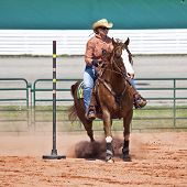 image of barrel racing  - Western horse and rider competing in pole bending and barrel racing competition - JPG