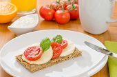 Crispbread with tomato and mozzarella on a breakfast table