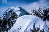 Closeup Aerial View of Snow Packed Craggy Mountain Peaks in the Great Alaskan Wilderness
