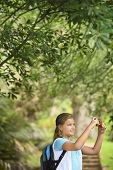 Side view of young girl taking photos through digital camera in forest