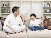 stock photo of legs crossed  - father and son having a conversation on couch at home - JPG