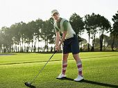Full length of young female golfer teeing off on golf course