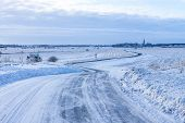 stock photo of icy road  - Countryside road through winter field with forest and church on the horizon - JPG