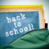 sentence back to school written in a blackboard with a wooden frame, in a schoolbag, with a retro ef