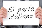 a man wearing a suit holding a signboard with the sentence si parla italiano, we speak italian, writ