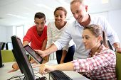 stock photo of classmates  - Teacher with students in computing class - JPG