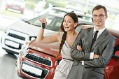 image of showrooms  - Happy young couple with keys from new car after automobile purchase in dealer showroom - JPG