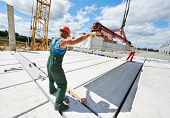 foto of labourer  - builder worker in safety protective equipment installing concrete floor slab panel at building construction site - JPG