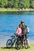 Smiling teenager bikers hugging at lakeside