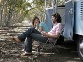pic of campervan  - Happy young couple sitting on deck chairs beside campervan parked at roadside - JPG