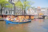 AMSTERDAM - APRIL 30: Amsterdam canals full of boats and people in orange during the celebration of queensday on April 30, 2013 in Amsterdam, The Netherlands