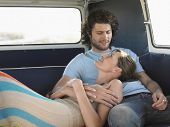 stock photo of campervan  - Affectionate young couple relaxing in campervan - JPG