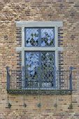 stock photo of scrollwork  - Tudor Style Windows with Rod Iron Scrollwork Metal Balcony on Exterior Brick Wall - JPG