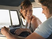 image of campervan  - Cheerful young couple sitting in campervan - JPG