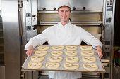 Baker In Bakery With Baking Plate Full Of Pretzels