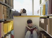 Male and female students reading books in the library