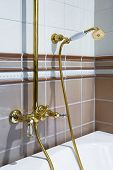 stock photo of bib tap  - The beautiful bronze faucet and white bath - JPG