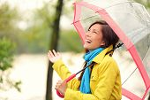 stock photo of outerwear  - Woman happy with umbrella under the rain during Autumn forest walk - JPG