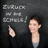Zuruck in die Schule - German teacher woman. Back to School written in German on blackboard by femal