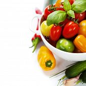 Assorted colorful tomatoes and vegetables in colander on white background - healthy eating concept
