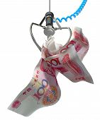 image of arcade  - An robotic claw from an arcade type game gripping a wad of creased chinese yuan notes on an isolated white background - JPG