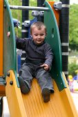 stock photo of children playing  - Children playing in the park on colorful slide - JPG