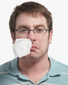 stock photo of blowing nose  - Sick young man with a tissue hanging from nose - JPG