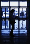 Silhouette Of Woman On Background Of Windows In Business-centre
