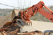 stock photo of track-hoe  - A track hoe excavator using its claw thumb to tear down an old hotel to make way for a new commercial development - JPG