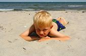 The Boy Lies On The Sea Beach