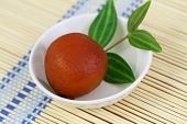 stock photo of gulab  - Gulab jamun dessert in bowl on bamboo mat, closeup