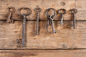 Rusty old keys hanging against a wooden background