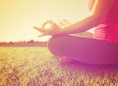 image of sunrise  -  hands of a woman meditating in a yoga pose on the grass toned with a soft instagram like filter - JPG