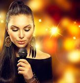Beautiful Singing Girl. Beauty Woman with Microphone over Blinking bokeh golden night background. Glamour Model Singer. Karaoke song