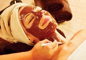 Chocolate Luxury Spa. Facial Mask. Spa therapy for young woman with cosmetic mask at beauty salon. W