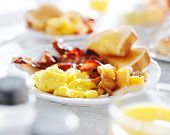 plate of breakfast food with bacon, eggs, toast, and fried potatoes