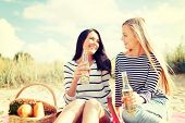 summer, holidays, vacation, happy people concept - smiling girlfriends with bottles of beer or non-alcoholic drinks on the beach