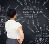Thoughtful businesswoman against blackboard with business buzzwords