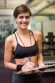Fit trainer taking notes and smiling at camera at the gym