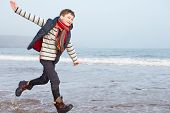 Young Boy Running Along Winter Beach