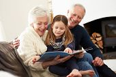 stock photo of granddaughters  - Grandparents And Granddaughter Reading Book At Home Together - JPG