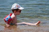 GREECE - JUNE 26: Boy with armbands, cap and sunglasses enjoying in the shallow sea water a sunny da