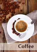 Cup of coffee with milk and coffee beans on napkin on wooden background