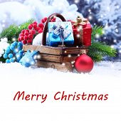 Composition with Christmas decorations in basket and fir tree on light background