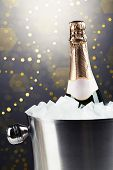 Bottle of champagne in bucket with ice, on bright background