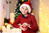 Little boy in Santa hat near fireplace in room