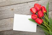 Fresh tulips and greeting card over wooden table background