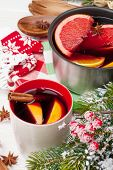 Christmas mulled wine on wooden table with fir tree and decor