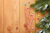 Christmas wooden background with snow fir tree and candies. View from above with copy space