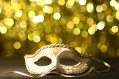 Beautiful carnival mask on table on golden background